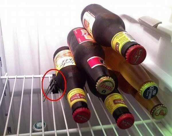 Beer bottles stacked in a fridge using a binder clip to hold them in place