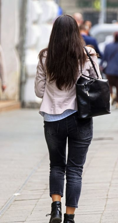 a girl walking with black bag