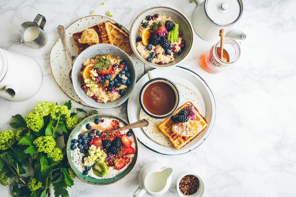 A table topped with plates of food and bowls of food