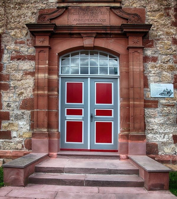 A red door with stone wall